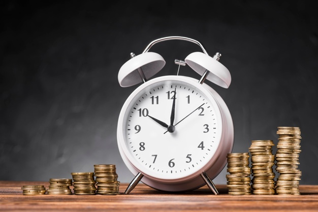 white-alarm-clock-increasing-stack-coins-wooden-table-against-gray-background_23-2147943427